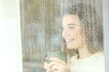Smiley positive teen holding a coffee mug looking outdoors through a window in a rainy day Foto de archivo