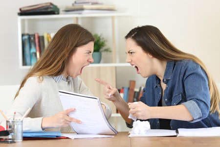 Two angry students arguing doing homework at home