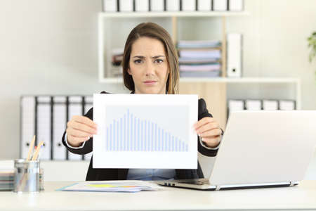 Front view of a worried executive showing a bad sales results chart at office Stok Fotoğraf - 101653774