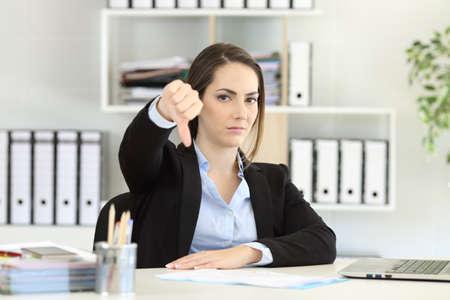 Vorderansicht Porträt einer verärgerten Geschäftsfrau, die mit Daumen unten im Büro leugnet Standard-Bild