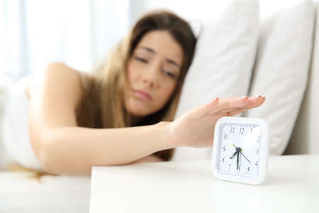 Sleepy girl waking up turning off alarm on a bed at home Stock Photo