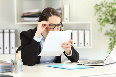 Office employee wearing eyeglasses with bad graduation having eyesight problems reading a letter