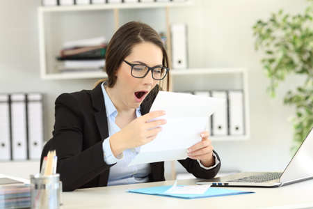 Bored office worker yawning reading documents sitting in a desktop at workplace