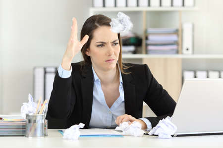 Frustrated executive without inspiration throwing a paper ball at office Imagens