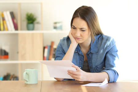 Portrait of a worried female reading a paper letter on a table at home Standard-Bild - 101053576
