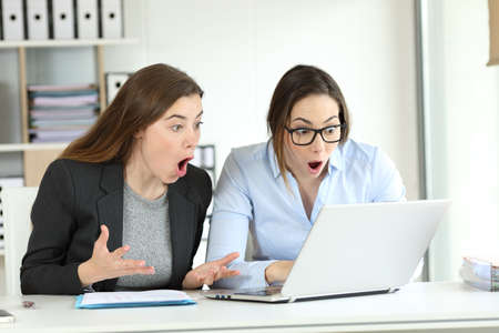 Surprised office workers reading together online news in a laptop