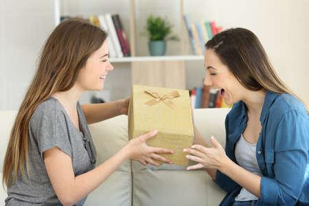 Chica emocionada recibiendo un regalo de un amigo sentado en un sofá en la sala de estar de casa