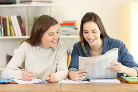 Two happy students reading news in a newspaper at home