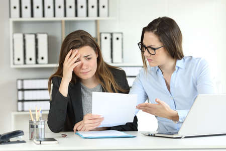 Boss scolding an intern showing a document at office Stockfoto