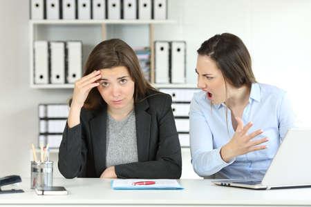 Chef schimpft mit einem Mitarbeiter, der im Büro auf die Kamera schaut