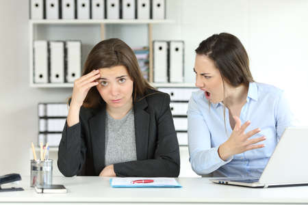 Szef beszta pracownika, który patrzy w kamerę w biurze