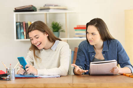 Angry student looking at her lazy mate who is playing with the smart phone instead of working Archivio Fotografico