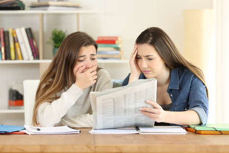 Two worried students reading bad news in a newspaper at home