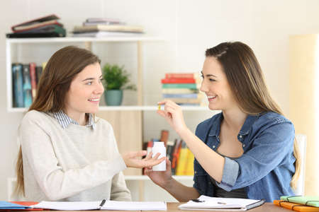Student studying and offering a vitamin supplement to a friend at home Banco de Imagens