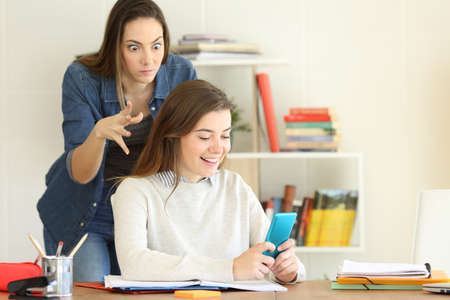 Angry student trying to kill her lazy mate who is playing with the smart phone Stock Photo