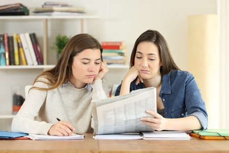 Two bored students wasting time reading news in a newspaper at home