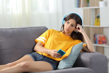 Serious teen listening to music online looking away sitting on a couch in the living room at home
