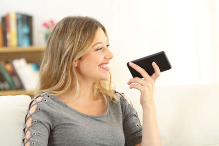 Girl talking to a phone using voice recognition sitting on a couch in the living room at home