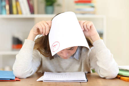 Front view of a sad student covering head with a failed exam at home