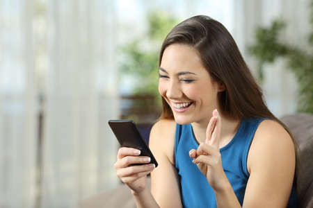 Hopeful woman waiting for online news in a smartphone sitting on a couch in the living room at home  Stock Photo