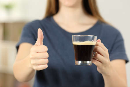 Front view close up of a woman hands holding a coffee cup with thumbs up at home