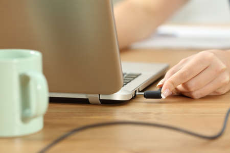 Close up of woman hands plugging charger in a laptop