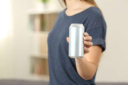 Primer plano de una mano de mujer sosteniendo una lata de refresco en casa