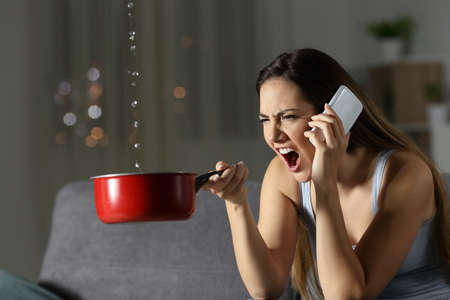 Angry woman calling insurance for water leaks sitting on a couch in the living room at home