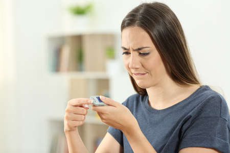 Diabetic girl checking blood sugar level with a glucometer