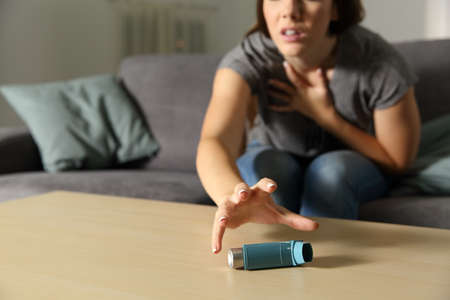 Asmathic girl catching inhaler having an asthma attack sitting on a couch in the living room at home Stock Photo