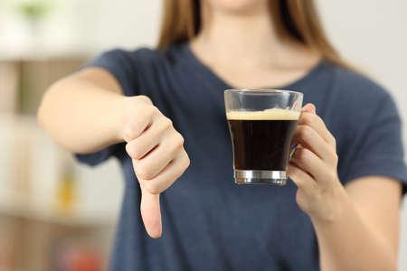 Vista frontal de cerca de las manos de una mujer sosteniendo una taza de café con los pulgares hacia abajo en casa Foto de archivo