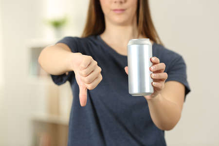 Front view close up of a woman hands holding a soda drink can with thumbs down at home Foto de archivo