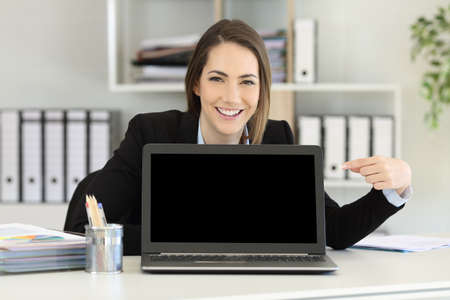Front view portrait of a happy office worker pointing at a laptop screen mockup