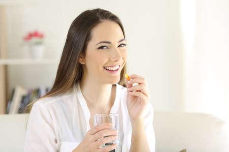 Donna felice che prende una pillola di integratore vitaminico ti guarda seduto su un divano nel soggiorno di casa Archivio Fotografico - 101678622