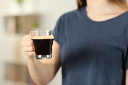Closeup of a woman hands holding a transparent coffee cup at home