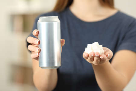 Front view close up of a woman hands holding a soda drink can and sugar cubes at home Stock Photo
