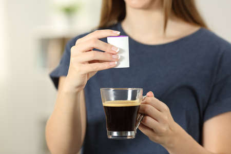 Front view close up of a woman hands throwing saccharin into a coffee cup at home Stock Photo