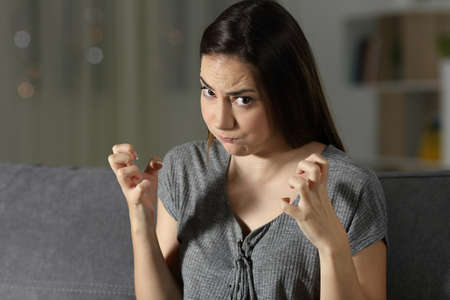 Furious woman looking at camera at home in the night sitting on a couch in the living room at home
