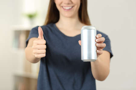 Front view close up of a woman hands holding a soda drink can with thumbs up at home Foto de archivo - 101678053
