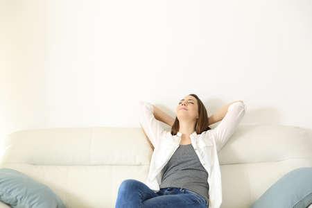 Weitwinkelansicht Porträt einer Frau, die auf einer Couch mit Kopierraum oben entspannt