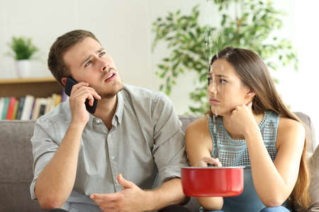 Desperate couple callling to insurance worried about home leaks in the living room Stock Photo - 102076775