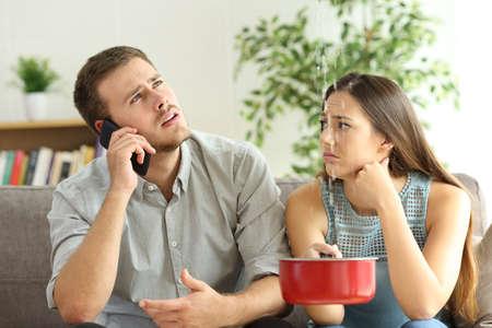 Una coppia disperata che si rivolge all'assicurazione preoccupata per le perdite a casa nel soggiorno Archivio Fotografico - 102076775