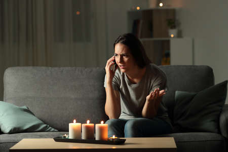 Angry woman calling insurance in the night after blackout sitting on a couch at home