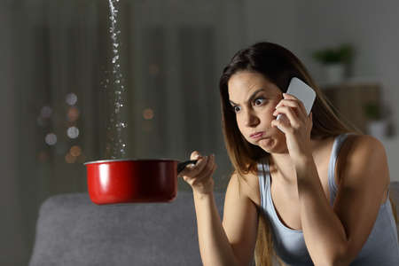 Furious woman claiming insurance for water leaks sitting on a couch in the living room at home Stok Fotoğraf