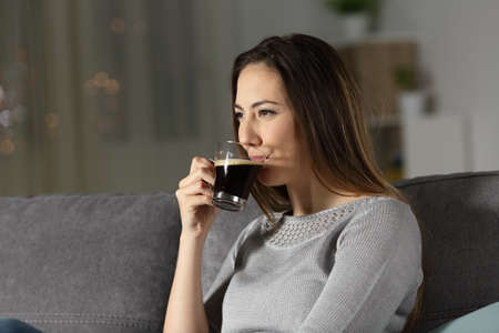 Relaxed woman drinking decaffeinated coffee in the night sitting on a couch in the living room at home Imagens
