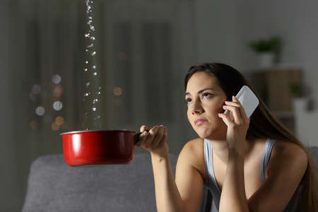 Frustrated woman claiming insurance for water leaks sitting on a couch in the living room at home Stock Photo