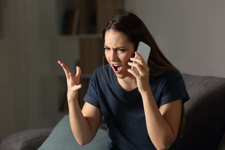 Angry customer claiming on the phone sitting on a couch in the living room at home Banque d'images - 102076821