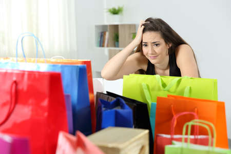 Worried shopaholic woman after multiple purchases in colorful shopping bags at home