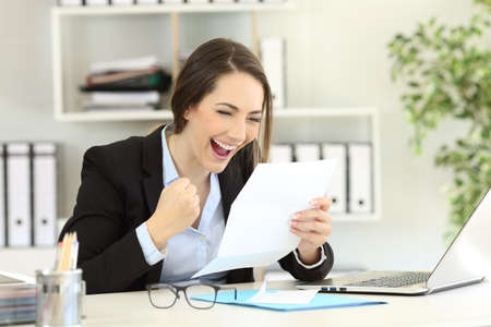Excited office worker reading good news in a letter Stock Photo