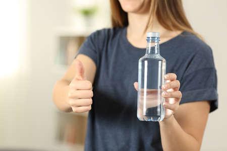 Manos de mujer sosteniendo una botella de agua con pulgares arriba en casa Foto de archivo - 102076848
